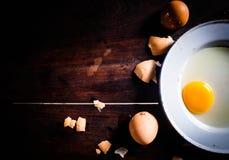 在一块白色板材的新鲜的鸡蛋在一个木地板上 库存照片