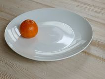 在一块白色板材的明亮的橙色萨摩烧在桌上 库存照片