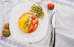 在一块白色板材的杯形蛋糕用草莓和猕猴桃 免版税库存照片