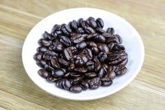 在一块白色板材的浓咖啡豆 图库摄影
