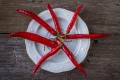 在一块白色板材的炽热辣椒,在老木桌上 免版税图库摄影
