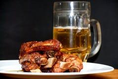 在一块白色板材的烤猪肉肋骨有一个投手的啤酒 库存照片