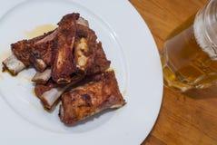在一块白色板材的烤猪肉肋骨有一个投手的啤酒 图库摄影