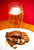 在一块白色板材的烤猪肉肋骨有一个投手的啤酒 免版税库存照片