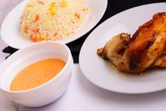 在一块白色板材的烤鸡用调味汁和意大利煨饭 图库摄影