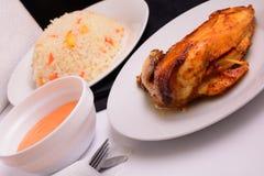 在一块白色板材的烤鸡用调味汁和意大利煨饭 库存照片