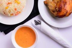 在一块白色板材的烤鸡用调味汁和意大利煨饭 免版税库存照片