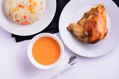 在一块白色板材的烤鸡用调味汁和意大利煨饭 免版税库存图片