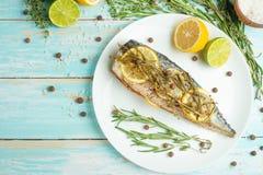 在一块白色板材的煮熟的鲭鱼用香料、草本、柠檬、石灰和盐 顶视图、空间复制的或者菜单 免版税库存照片