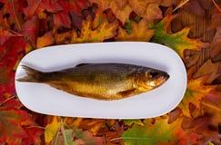 在一块白色板材的熏制的鱼 库存照片