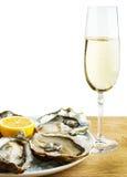 在一块白色板材的牡蛎用柠檬和一杯在一张木桌上的酒 库存图片