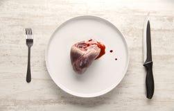 在一块白色板材的猪肉心脏 库存照片