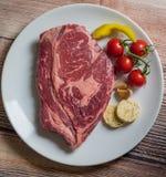 在一块白色板材的粗暴牛肉肉 免版税库存图片