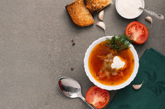 在一块白色板材的红色汤在一张灰色桌上,顶视图 新鲜的罗宋汤用蕃茄和油煎方型小面包片 免版税库存照片