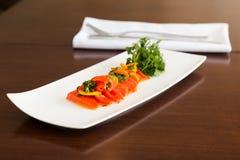 在一块白色板材的红鲑鱼crudo盘用新鲜的草本 免版税库存照片