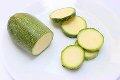 在一块白色板材的绿色南瓜切片 库存图片