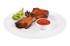 在一块白色板材的肉肋骨有调味汁和莴苣叶子的 免版税图库摄影