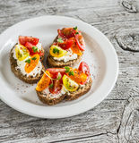 在一块白色板材的蕃茄和乳酪bruschetta在土气轻的木板 健康早餐,快餐 免版税库存图片
