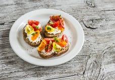 在一块白色板材的蕃茄和乳酪bruschetta在土气轻的木板 库存照片