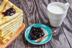 在一块白色板材的薄煎饼用蜂蜜和一个杯子牛奶 鲜美增殖比 免版税库存图片