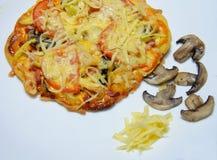 在一块白色板材的薄饼 蘑菇和干酪 免版税库存图片