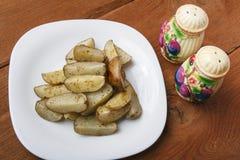 在一块白色板材的被烘烤的土豆 在木背景的有机素食食物 库存图片