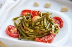 在一块白色板材的被烘烤的菜在烤箱-豆,土豆,葱,蕃茄烹调了 在空白表面 装饰用新鲜的大蒜 免版税库存图片