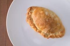 在一块白色板材的被烘烤的菜肉馅饼 免版税库存图片