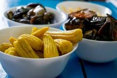 在一块白色板材的韩国食谱用卤汁泡的黄色迷你玉米在一张蓝色桌上 库存图片