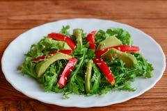 在一块白色板材的鲕梨、芝麻菜和胡椒沙拉 简单的芝麻菜和鲕梨沙拉用红辣椒和芝麻籽 原始的食物 库存图片