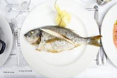 在一块白色板材的整个白色鱼 免版税库存照片