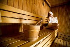 在一块白色毛巾包裹的少妇放松在木蒸汽浴ro 免版税库存图片