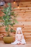 在一块白色毛巾包裹的婴孩坐木背景在罐的一棵竹树附近 图库摄影