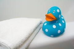 在一块白色毛巾旁边的逗人喜爱的橡胶鸭子在卫生间里 免版税库存图片