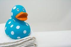 在一块白色毛巾的逗人喜爱的橡胶鸭子在卫生间关闭 免版税库存图片