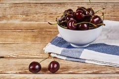 在一块白色碗和小垫布的樱桃 免版税库存照片