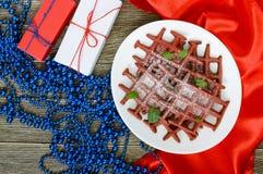 在一块白色陶瓷板材的巧克力美国人奶蛋烘饼`红色天鹅绒`在木背景 免版税库存图片