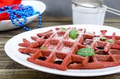 在一块白色陶瓷板材的巧克力美国人奶蛋烘饼`红色天鹅绒`在木背景 免版税图库摄影