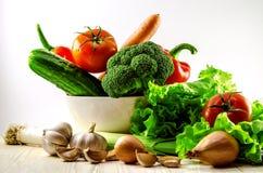 在一块白色陶瓷板材的新鲜蔬菜烹调的salata 木表面上说谎葱和大蒜 库存照片