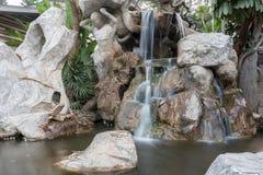在一块石头的瀑布行动在庭院里 库存图片