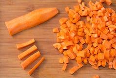 在一块砧板的切成小方块的未加工的红萝卜 图库摄影