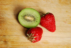 在砧板的草莓和猕猴桃 免版税图库摄影
