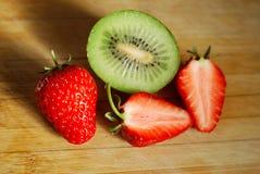 在砧板的草莓和猕猴桃 免版税库存照片