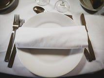 在一块空的圆的白色板材的餐巾有在边的利器的 库存图片