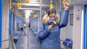 在一块空的地铁的妇女乘驾和浏览在她的智能手机 站立并且拿着扶手栏杆 股票录像