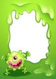 在一块空的模板前面的一个独眼的绿色妖怪 免版税库存照片