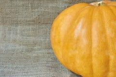 在一块粗麻布的秋天南瓜在一个土气样式 免版税库存图片