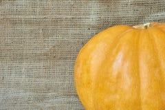 在一块粗麻布的秋天南瓜在一个土气样式 库存图片