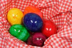 在一块红色和白色餐巾的五颜六色的复活节彩蛋 免版税图库摄影