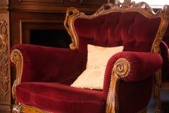 在一块红色布料布置的一把古老木椅子 免版税图库摄影